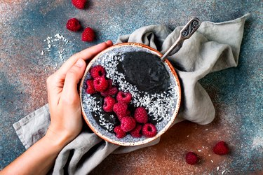 Activated charcoal smoothie and chia seed pudding bowl, vegan detox dessert with raspberry and coconut milk. Overhead, top view, flat lay
