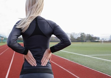 Back Pain. Athletic fitness woman rubbing lower back.