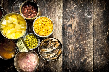Various canned vegetables, meat, fish and fruits in tin cans.