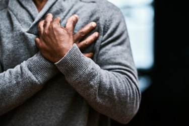 An older man holding his chest, suffering from a heart attack brought on by high blood pressure