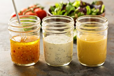 Three types of homemade low-carb salad dressings in glass jars