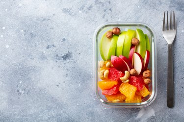 Fruits salad and nuts in a glass container. Healthy eating.