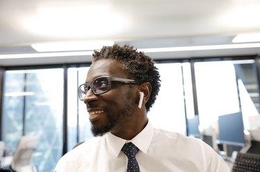 Businessman smiling, wearing earbud headphones, looking at laptop