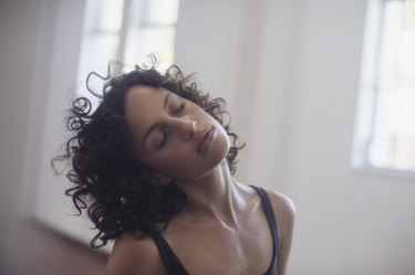 Calm young female dancer stretching neck in dance studio