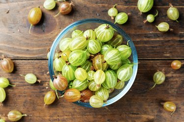 Ripe fiber-rich gooseberry in a glass bowl on wooden table