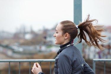 a sporty young woman runs through the city