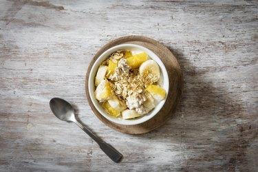 Bowl of granola with oat flakes, natural yoghurt, ananas and banana