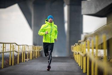 Male athlete running over the bridge