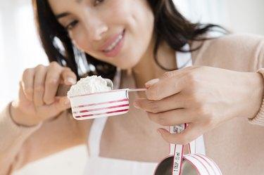 Hispanic woman measuring flour substitutes
