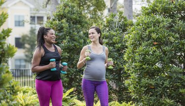 Two pregnant women exercising together, power walking