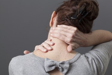 Woman rubbing the back of her neck with her hands