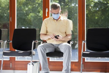 man with face mask sitting in a bright waiting room