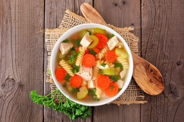 Homemade chicken noodle soup with vegetables, top view on a wood background