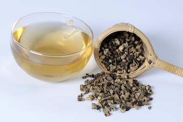 Cup of tea with dried black cohosh root and tea strainer, close up
