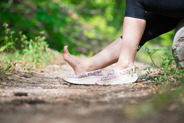 Pain in woman's foot, massage of female leg, injury while running, trauma during workout
