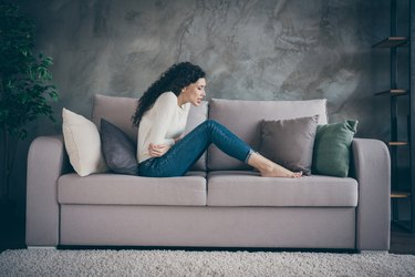Profile side view of her she attractive depressed unhealthy wavy-haired girl sitting on divan suffering from medical belly problem in modern loft industrial style interior living-room indoors
