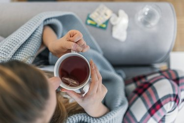 A woman drinking tea and resting to recover from the flu