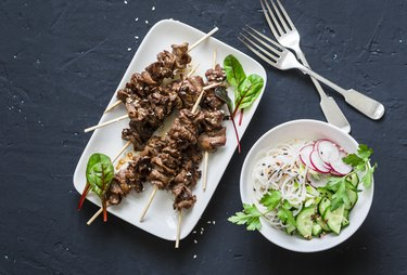 Asian style grilled beef skewers and vermicelli salad on a dark background, top view. Delicious appetizer, tapas, snack