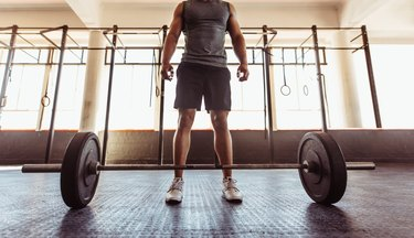 Man with barbell in health club