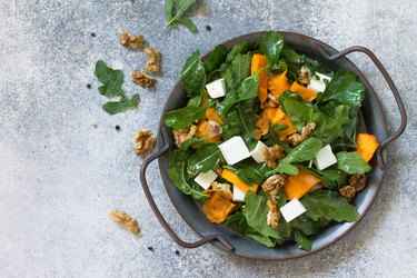 Concept diet menu, Vegan food. Salad with baked pumpkin, feta, cheese and vinaigrette dressing on stone background. Top view flat lay. Free space for your text.