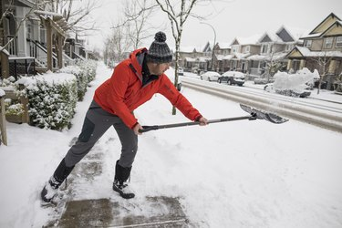 Man shoveling snow in winter and burning calories