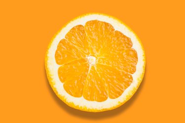 Close-Up Of Orange Slice Over Orange Background