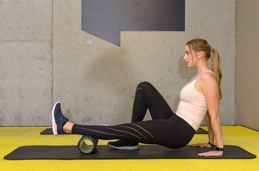Young woman exercising with roller at gym