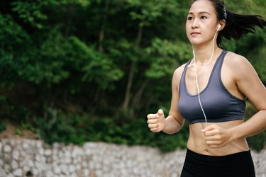 Young Asian woman running on the green countryside. Girl jogging workout at nature forest park