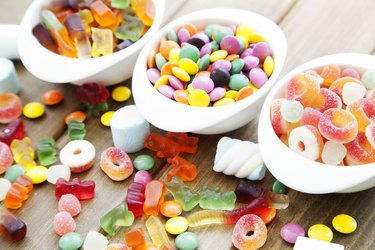 Colorful candies in oval white containers and scattered on wooden table