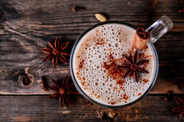 Homemade Chai Tea Latte with anise and cinnamon stick in glass mug. Top view