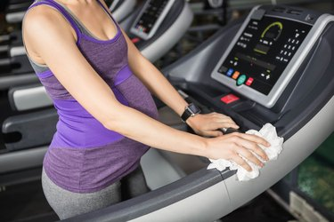 Mid section of pregnant woman cleaning treadmill