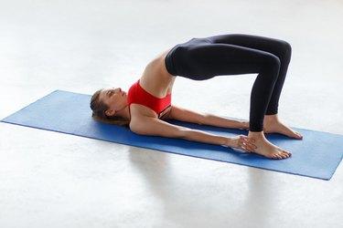 Beautiful female in Bridge Pose on floor