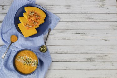 pumpkin cream soup in a blue plate on a white wooden background using light blue textile and spoons. flat lay. copy space