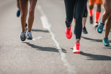 Group of unrecognizable athletes running a marathon on the road.
