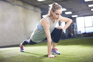 Woman warming up with stretching exercise in gym