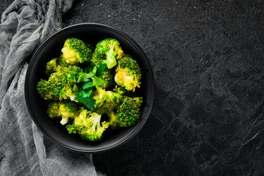 Boiled broccoli in a black plate. On a black background. Top view. Free space for your text.
