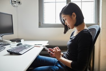 Young woman using smart phone at work.