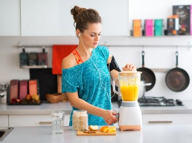 Fit woman in kitchen making a smoothie
