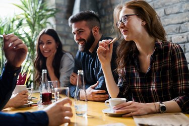 Happy young friends hangout in coffee shop