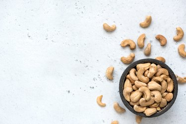 Cashew nuts in bowl on grey concrete background