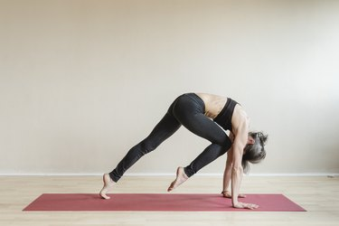 Woman doing Plank pose variation Knee to nose