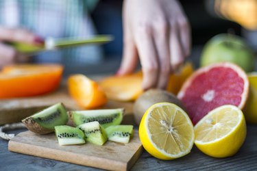Woman's hands cutting fresh fruits