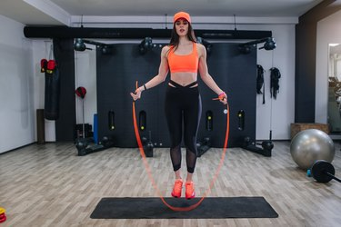 Young fit woman jumping a rope at a gym