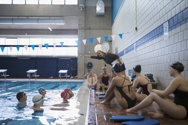 Female coach explaining stroke to swimmers in swimming pool at practice