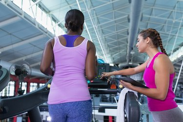 Female trainer assisting woman to work out on treadmill