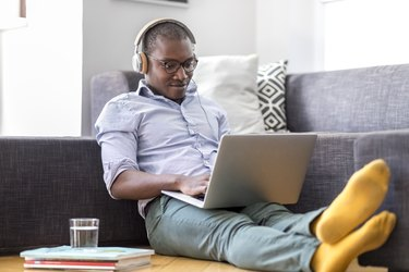 Young man sitting on the floor in the living room using laptop and headphones