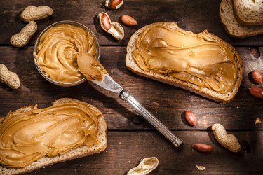 Peanut butter on toast shot on rustic wooden table