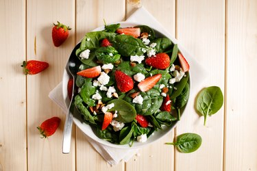 Healthy vegetable salad of fresh spinach, strawberries, feta cheese and almond on plate.