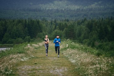 Trainer and female sportsman jogging outdoor