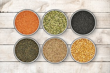 Six lentil bowls on wood background from directly above